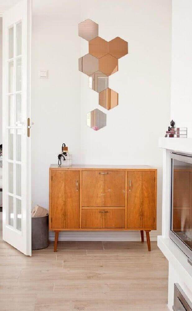 decoração com buffet de madeira e vários espelhos de bronze em formato de hexágono Foto Moody's Home
