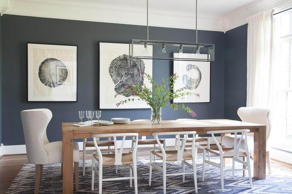 decoração com modelos diferentes de cadeiras para sala de jantar modernas com quadros na parede e mesa de madeira Foto Lonny