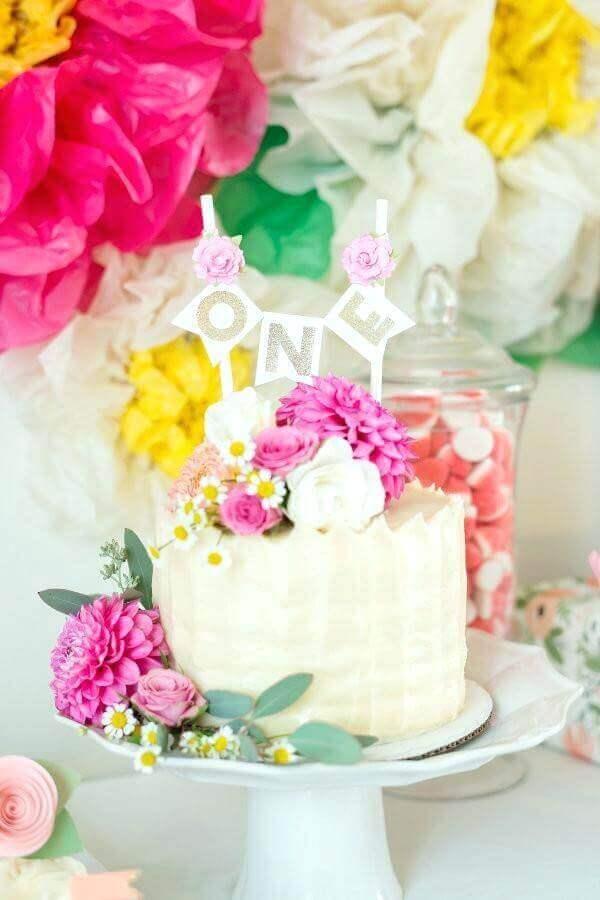 decoração com muitas flores para festa tropical com bolo branco Foto Costinc