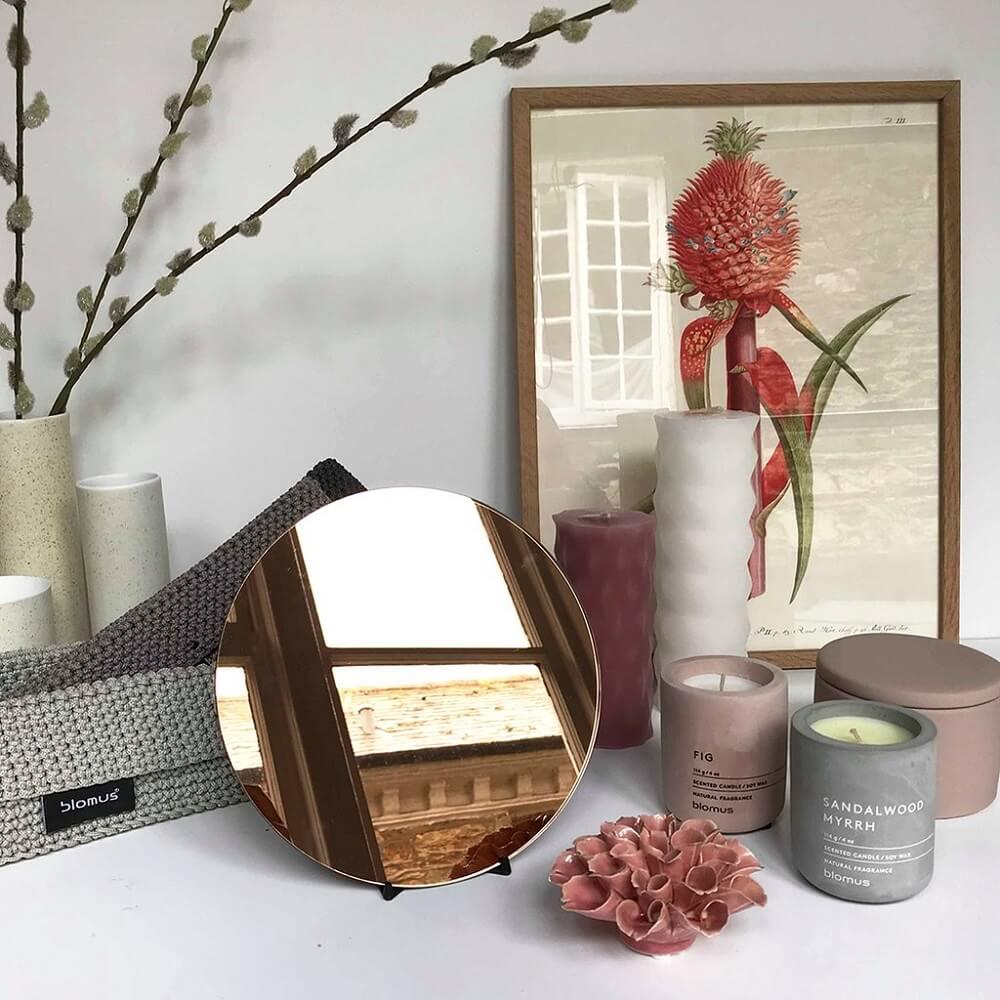 decoração com velas e pequeno espelho bronze redondo Foto The Clementine