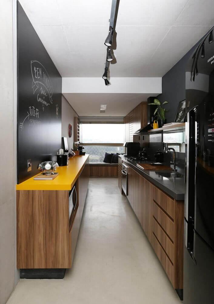 decoração cozinha corredor com parede de giz bancada amarela e armários de madeira Foto SP Estudio