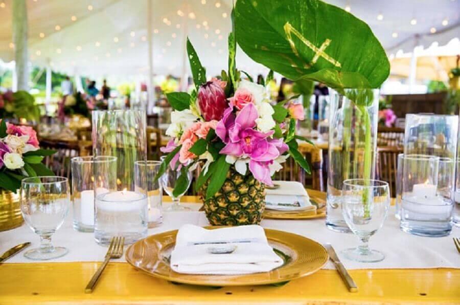 decoração de festa tropical com arranjo de flores feito em abacaxi Foto Internovias