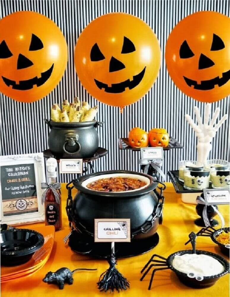 decoration for Halloween party with iron cauldron and orange balloons Photo Woodland Springs