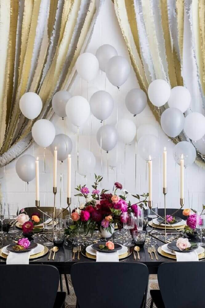 sophisticated party decoration with silver and white balloon panel with many flower arrangements on the table and candlesticks Foto Crate and Barrel