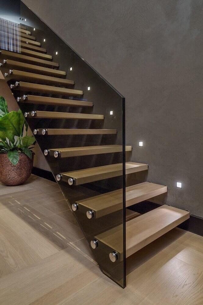 escada de madeira com iluminação próxima aos degraus e guarda corpo de vidro escuro Foto Pinterest