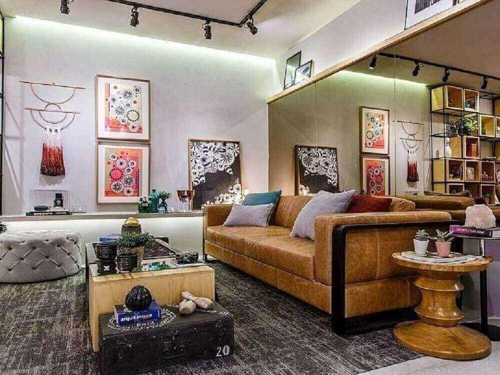 espelho bronze para sala de estar decorada com sofá de couro puff capitonê cinza e quadros diferentes Foto Pinterest