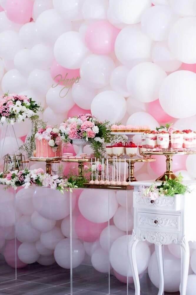 festa decorada com bexigas rosa e branca e arranjos de flores na mesa do bolo Foto Pinterest