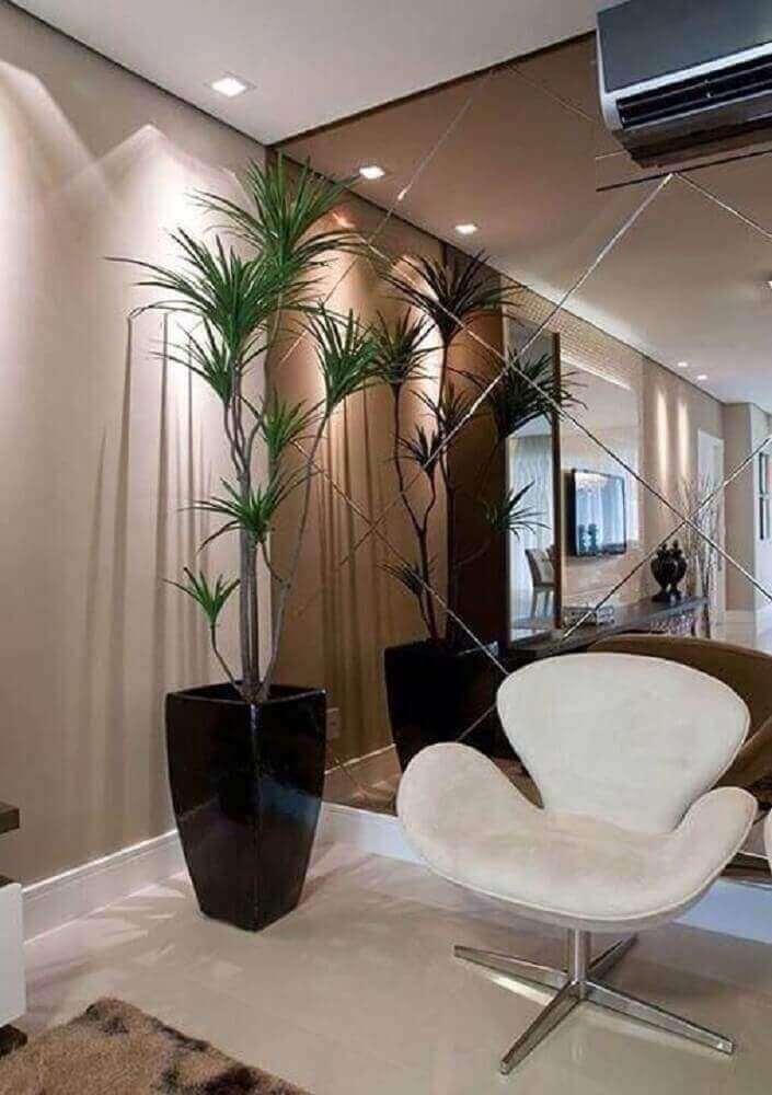 hall de entrada decorado com parede revestida de espelho bronze e cadeira branca Foto Nouw