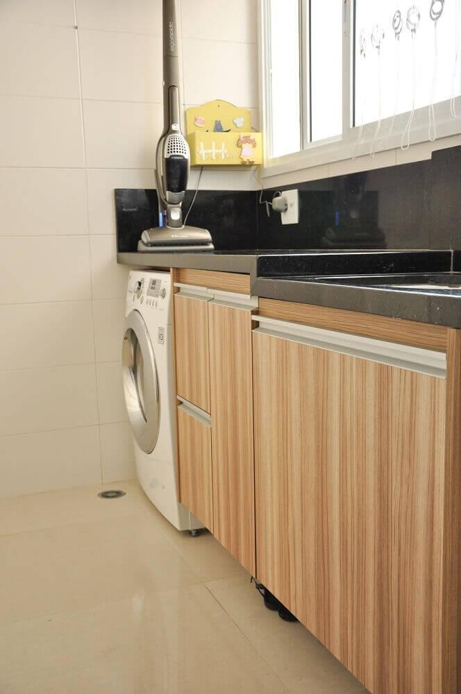 lavanderia planejada com bancada preta e armários que imitam madeira Foto DECORELLAS