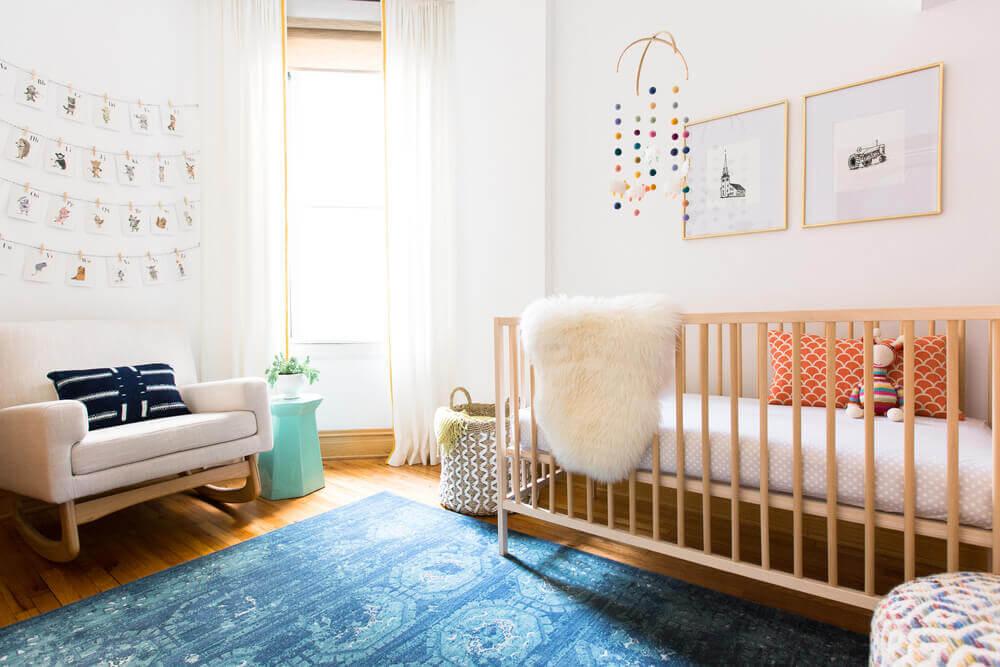 modelo confortável de cadeira de amamentação moderna para quarto de bebê com tapete azul Foto Rehabitat Interiors