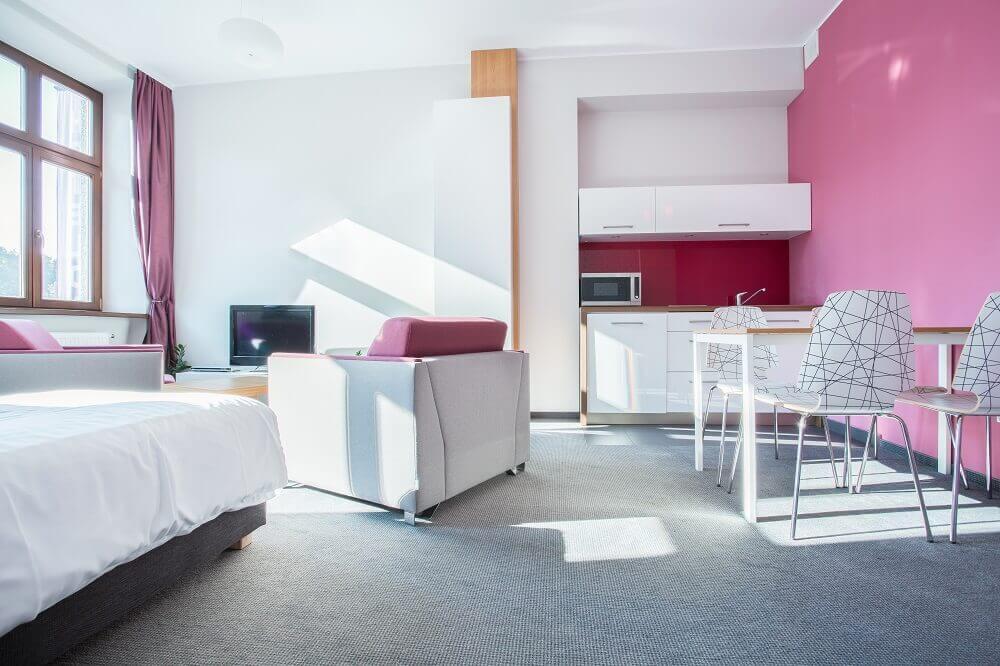 quitinete decorada com parede rosa e cadeira estampada