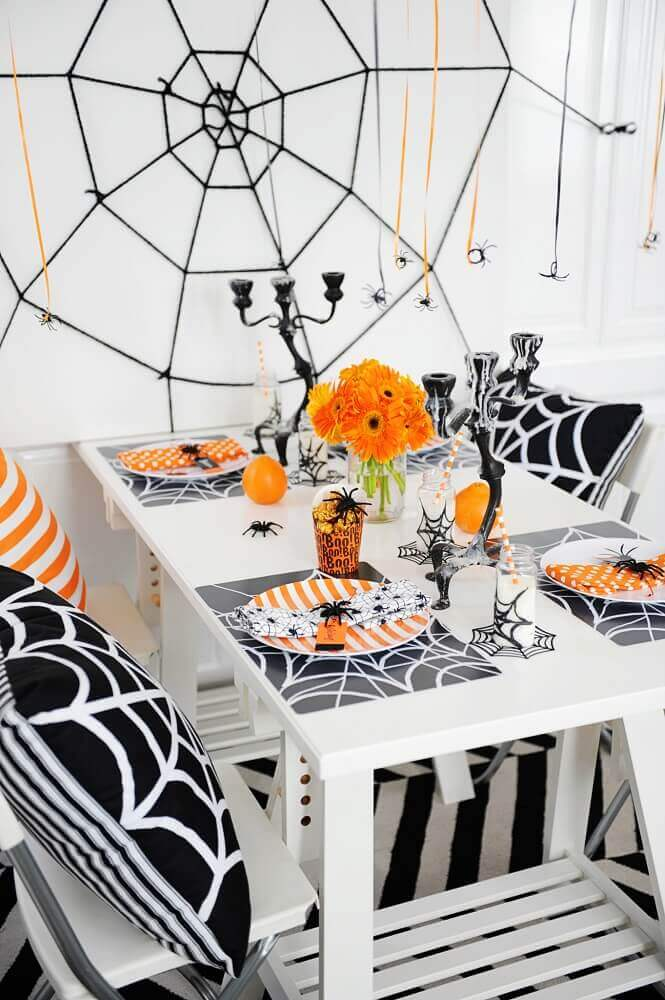 shades of orange arm and black for Halloween decoration with large web on the wall Photo Notey