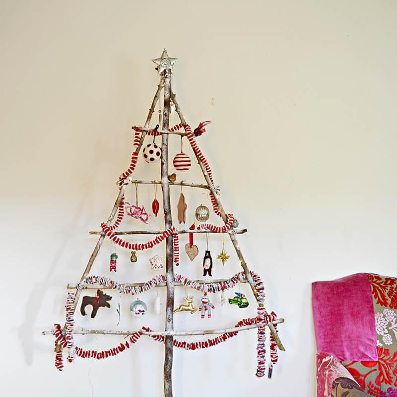 Árvore de natal artesanal com galhos e enfeites Foto de Pillar Box Blue
