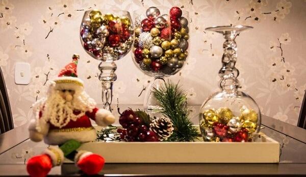 Mesa de jantar decorada com taças de vidro formam arranjos de Natal