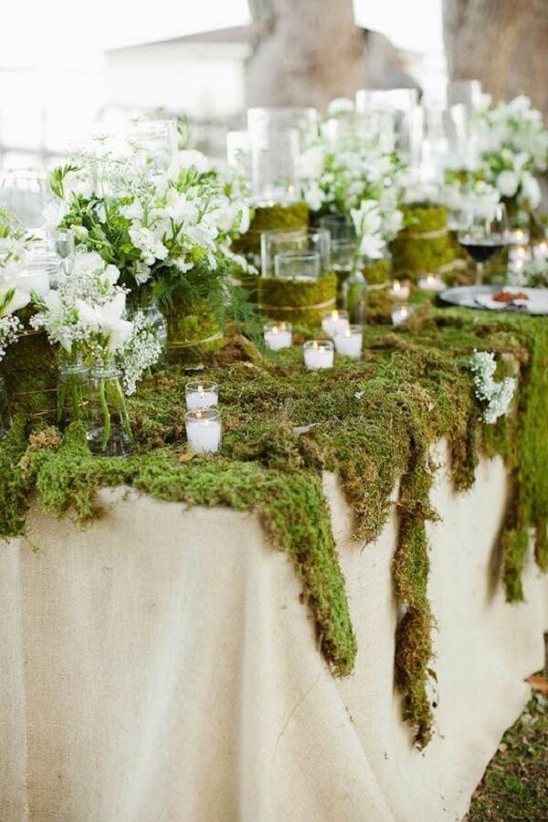 A decoração da mesa com musgos se destaca na festa jardim encantado