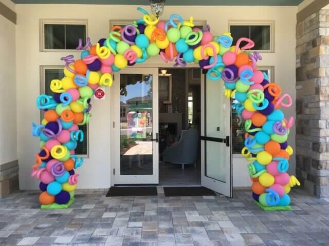 Arco de balões em decoração neon na entrada da festa Foto de Pinterest