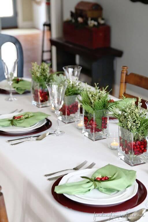 Cachepot de vidro com plantinhas verdes e vermelhas na mesa de ceia de natal Foto de Finding Home Online