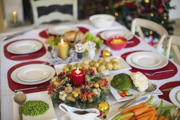 Ceia de natal com sousplat vermelho e toalha de mesa branca Foto de Nova24TV
