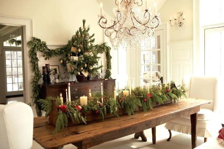 Centro de mesa de madeira com folhas velas em mesa de ceia de natal Foto de Just Cope