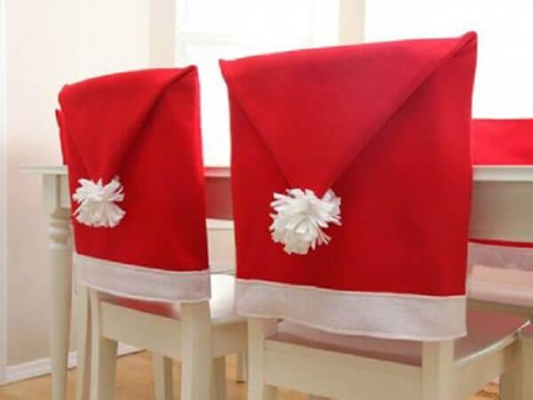 Decoração de natal simples e barata cadeiras revestidas com chapéu papai noel