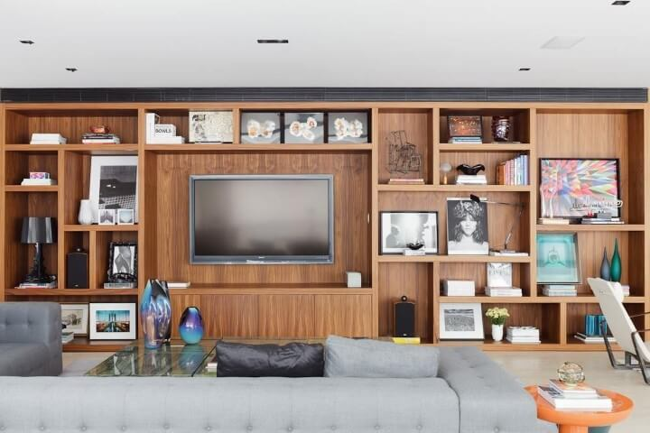 Decoração de sala com estante de madeira cheia de objetos de decoração Projeto de Suite Arquitetos