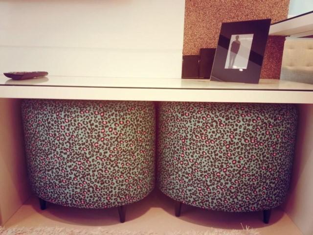 Decoração de sala com puffs de oncinha encaixados sob mesa Projeto de Condecorar