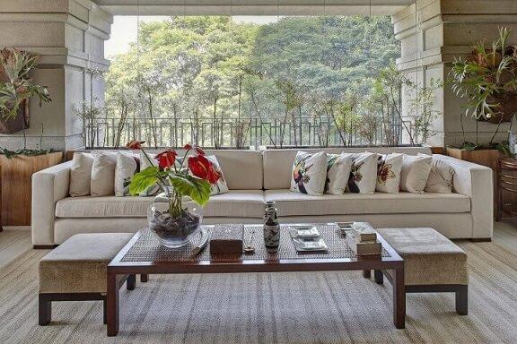 Decoração de sala com sofá branco e almofadas com estampas de pássaros Projeto de Ana Luisa Previde