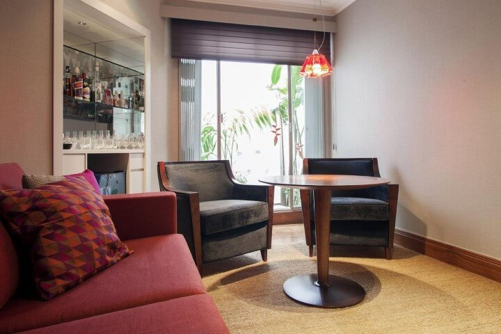Decoração de sala com sofá vermelho e poltronas pretas Projeto de Deborah Basso
