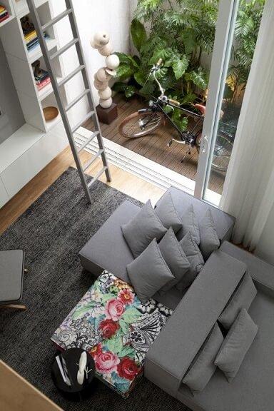 Decoração de sala com sofás cinzas e puff florido Projeto de Consuelo Jorge