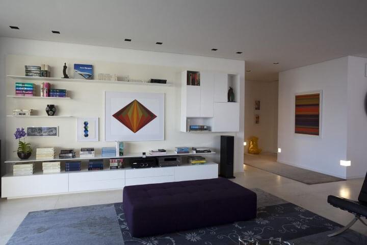 Decoração de sala de estar com várias pradeleitas e nichos com livros e objetos decorativos Projeto de AMC Arquitetura