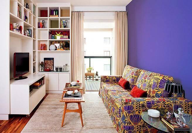 Decoração de sala pequena com estante, parede colorida e sofá estampado