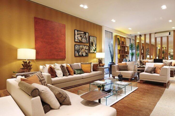 Decoração de sala sofisticada com parede dourada e várias almofadas coloridas Projeto de Quitete Faria