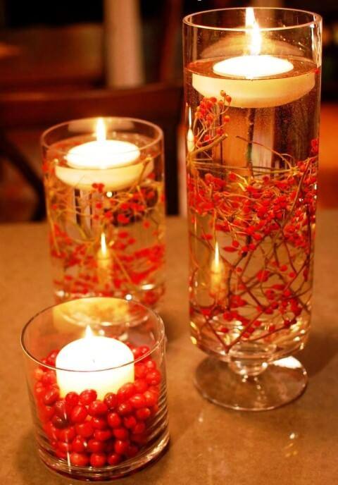 Enfeites de mesa com copos com velas e plantas vermelhas Foto de HomeBNC