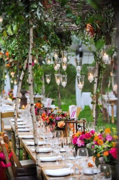 Festa externa com tema jardim encantado e mesas longas com decorações de flores e folhas Foto de Pinterest