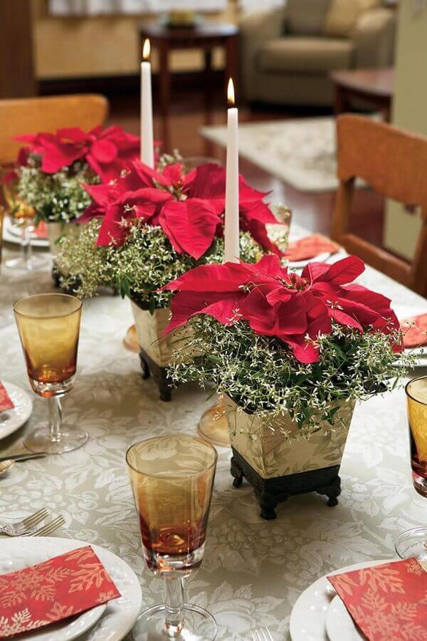 Flor de natal com vela decora a mesa de jantar