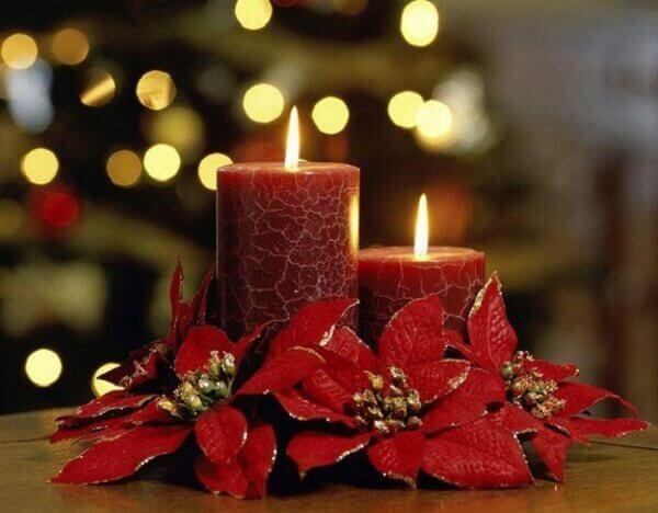 Flor de natal com velas na mesa de jantar