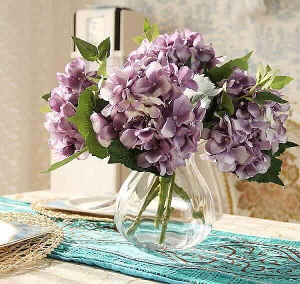 Flores artificiais em mesinha de canto