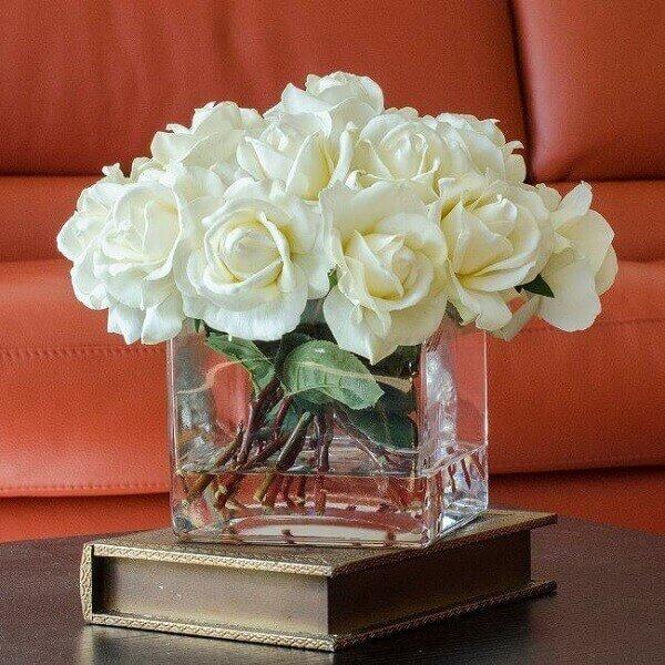 Flores artificiais em recipiente de vidro transparente