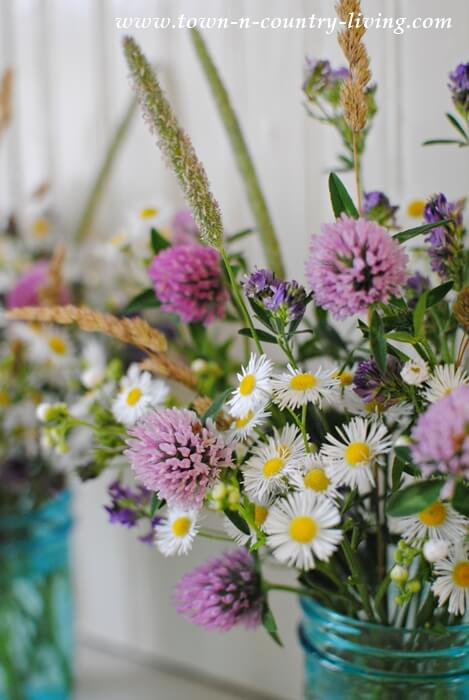 Flores de campo em vaso de vidro azul Foto de Town n Country Living