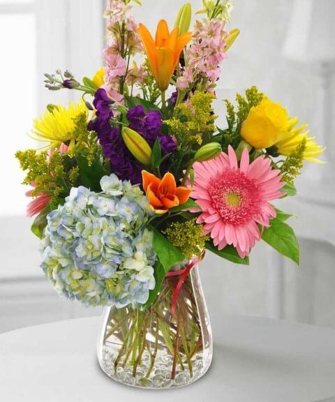 Flores do campo coloridas em vaso cheio de água Foto de Currans Flowers