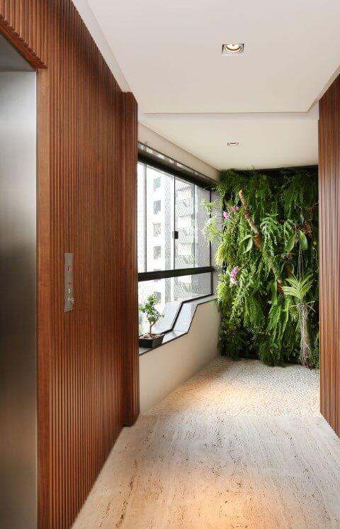 Hall com paredes de madeira e jardim vertical Projeto de Patricia Bergantin