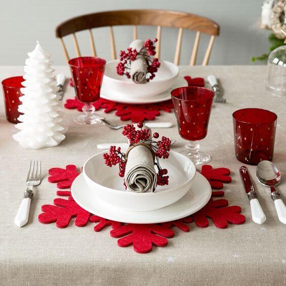 Mesa de ceia de natal com descansos de prato vermelhos em formato de floco de neve Foto de Inspira Hogar