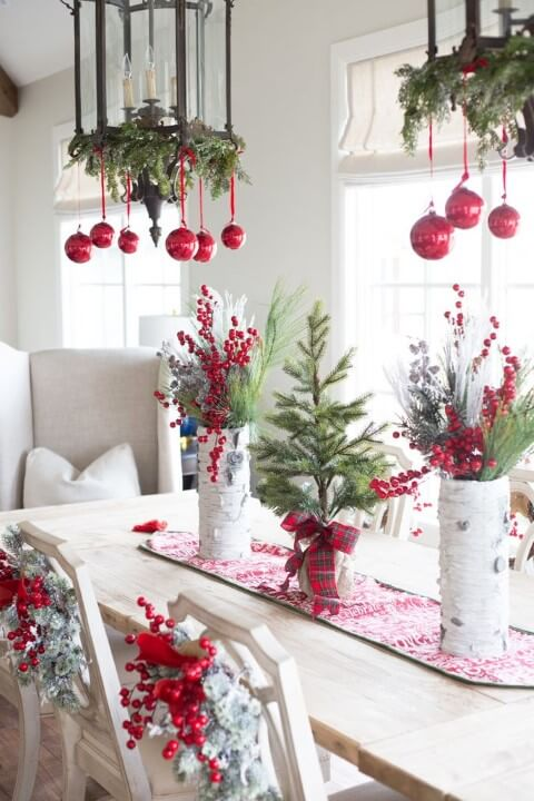 Christmas dinner table with ornaments in the lamps and in a treadmill in the center Photo by Alyssa Chia