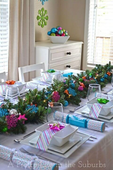 Mesa de ceia de natal com ramos de pinheiro e enfeites coloridos de natal Foto deA Pretty Life in the Suburbs