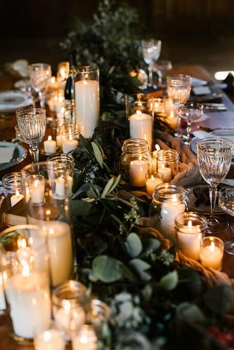 Christmas supper table with several candles and tree branches Photo of 100 Layer Cake