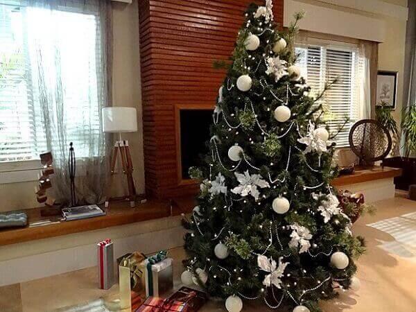 Pinheiro de Natal com enfeites branco em sala