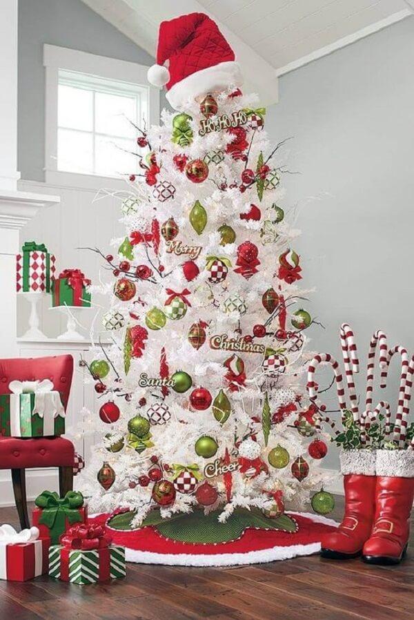 Pinheiro de natal branca repleto de enfeites natalinos em tons de vermelho e verde