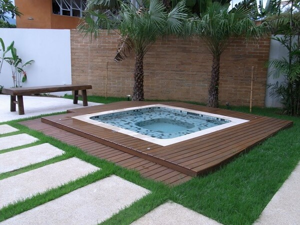 Piso com deck de madeira e parede com tijolinho