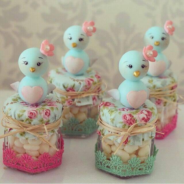 Potinhos de vidro com passarinhos de biscuit em decoração jardim encantado Foto de Pinterest