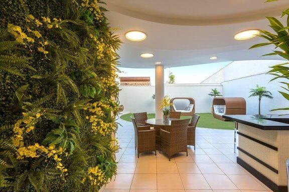 Quintal com jardim vertical com flores amarelas Projeto de Iara Kilaris